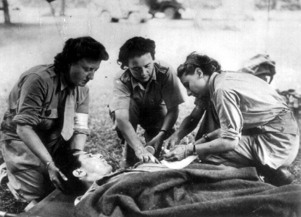 3 infirmières françaises de la Division Leclerc soignent un blessé.