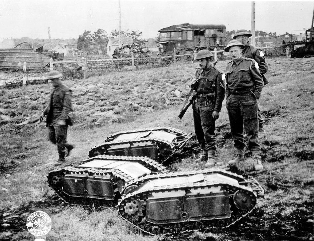 4 soldats alliés prennent la pose avec des véhicules tactiques chenillés allemands capturés. Ces derniers sont téléguidés par fil et équipés de 60 kg d'explosifs.
