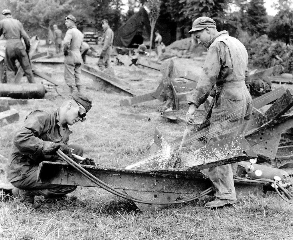 Des soudeurs-mécaniciens en combinaison de la 705th Ordnance Coy débitent des obstacles anti-chars (hérisson) grâce au chalumeau.