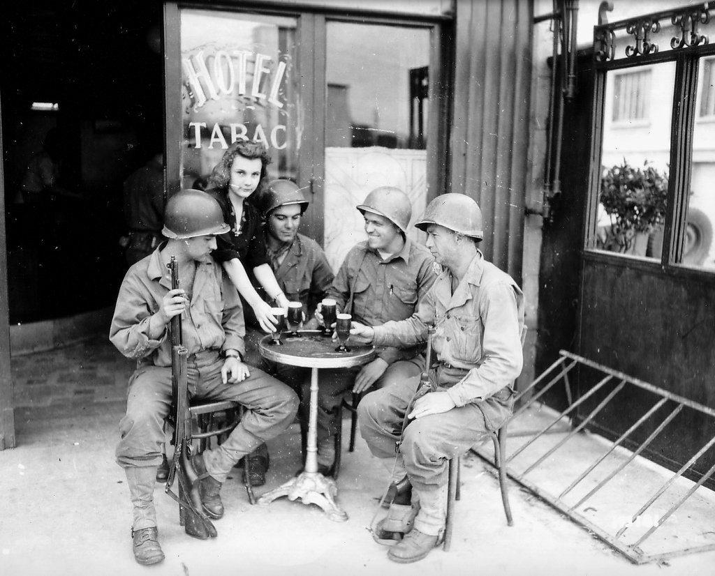 Quatre soldats de la 79th US ID se prélassent à la terrasse d'un café, avec leur bière pression.
