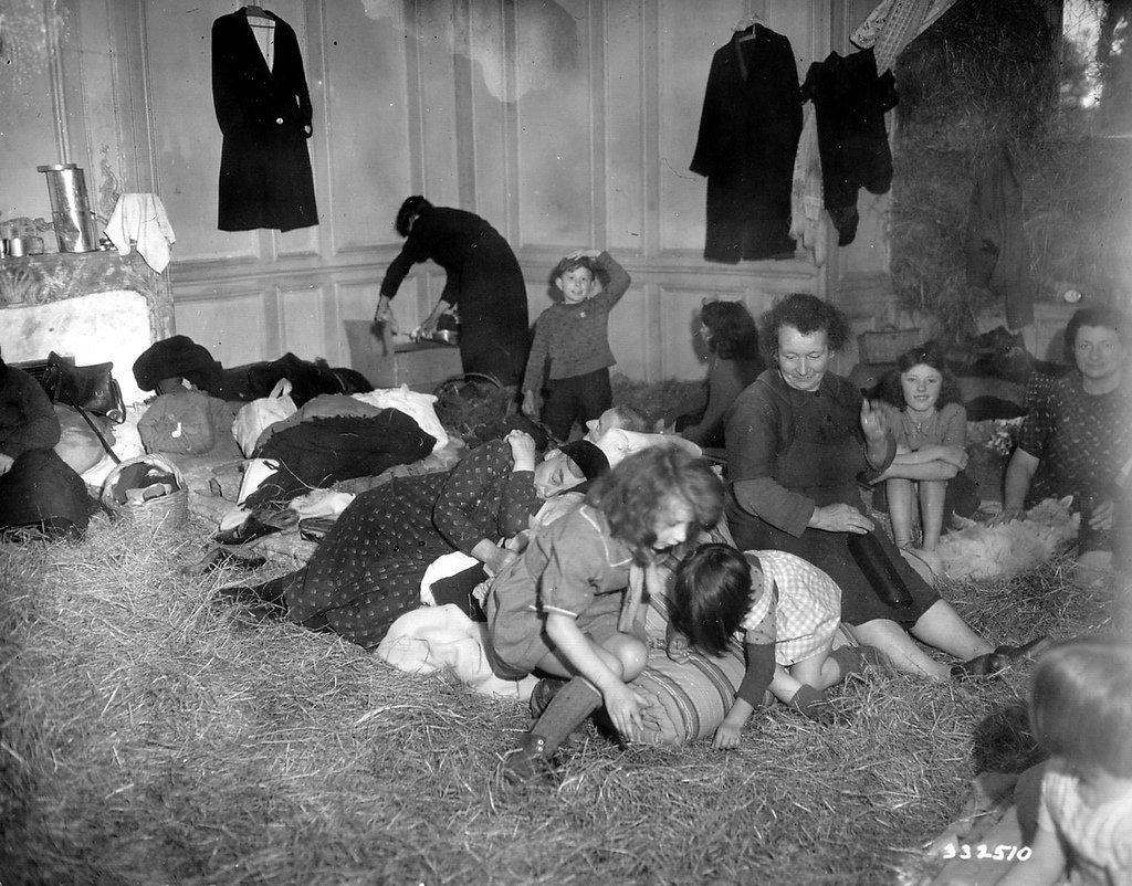 De la paille disposée au sol du salon d'une luxueuse habitation pour recevoir des réfugiés.