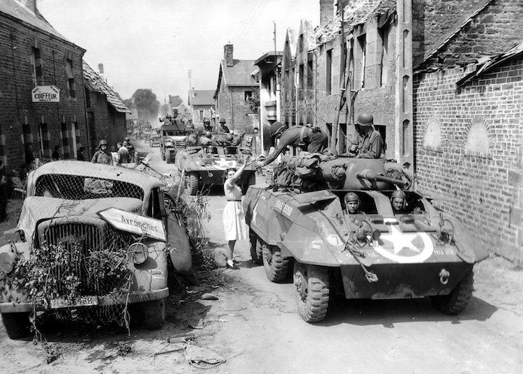 Une femme offrant de l'eau aux soldats de la 4ème division blindée, qui traversent Folligny (31 juin 1944).