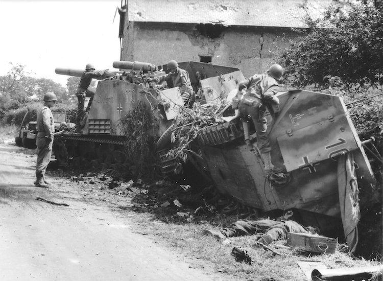 Quatre soldats US inspectent les véhicules neutralisés, deux corps allemands au sol.