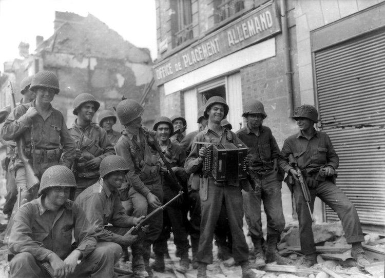 Des soldats fêtent la libération d'Argentan devant les ruines d'un office de placement allemand », destiné à enrôler des travailleurs à envoyer en Allemagne Nazie.