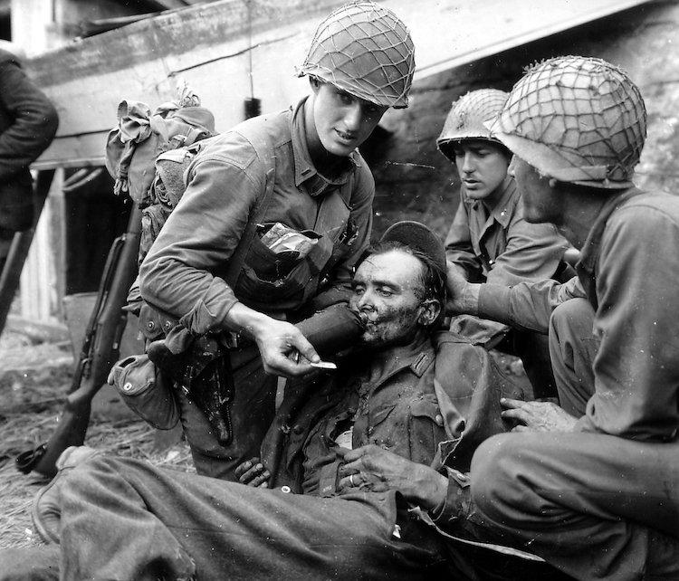 Le Lieutenant Stockridge Bacchus étanche la soif d'un soldat allemand blessé lors de la libération de Mantes. Derrière le soldat, on voit le Sergent Harril, responsable de la blessure.
