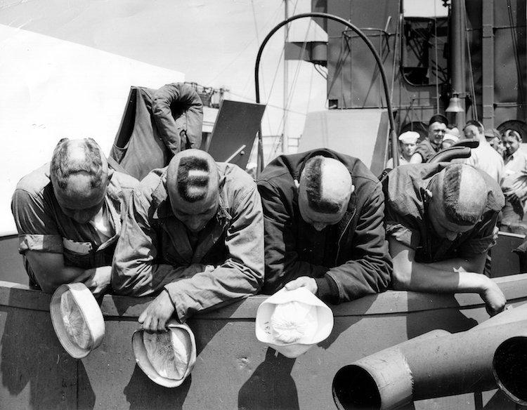 Quatre marins de l'US Navy découvrent leurs calottes avec le mot H.E.L.L. inscrit, signifiant ENFER.