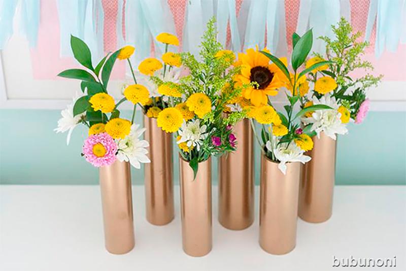 Fabriquer un centre de table décoratif en mettant au préalable de la peinture sur le tube. Il ne reste plus qu'à couvrir le bas du tube avec du carton et de la colle.