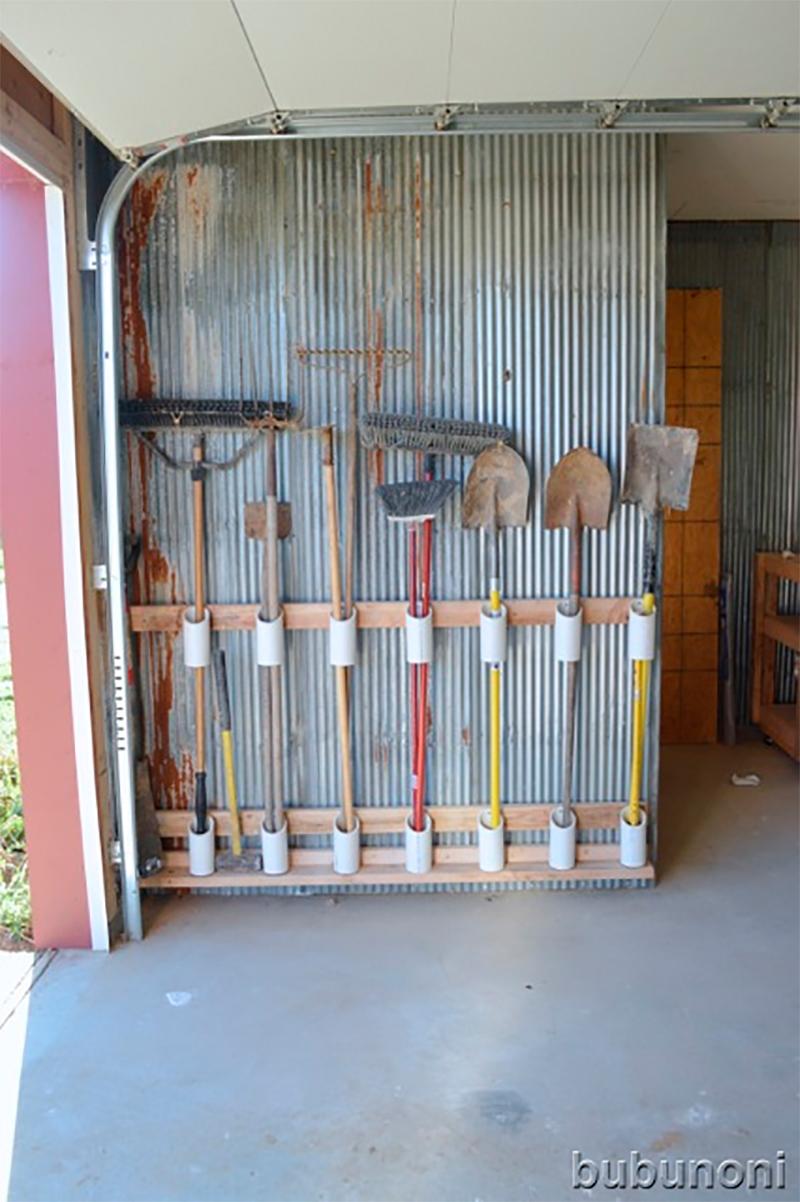 Créer un organiseur d'outils du jardin en fabriquant des tubes guides sur un cadre. Les fixer au mur à l'aide de colle ou vis pour sécurisé l'ensemble.